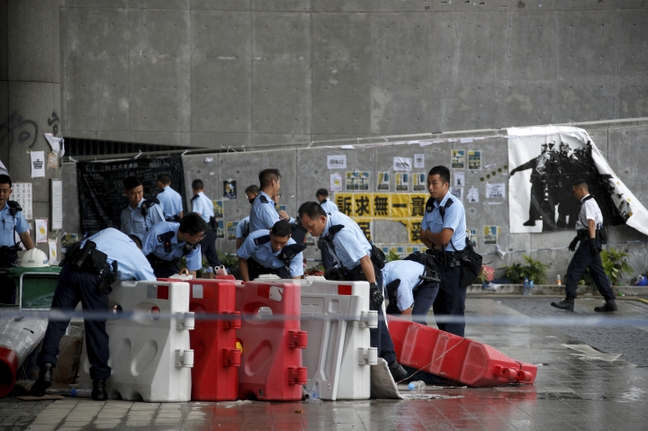 Policemen search for items used by protesters as they collect evidence outside the closed Legislative Council building in Hong Kong, Wednesday, July 3, 2019. A pro-democracy lawmaker who tried to stop Hong Kong protesters from breaking into the legislature this week says China will likely use the vandalizing of the building as a reason to step up pressure on the Chinese territory. (AP Photo/Andy Wong)