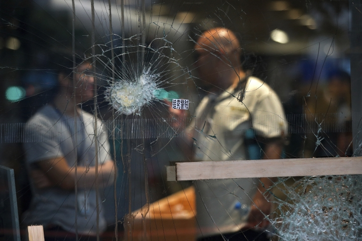 People chat with each other behind a broken glass panel damaged by protesters at the Legislative Council building in Hong Kong, Wednesday, July 3, 2019. A pro-democracy lawmaker who tried to stop Hong Kong protesters from breaking into the legislature this week says China will likely use the vandalizing of the building as a reason to step up pressure on the Chinese territory. (AP Photo/Andy Wong)
