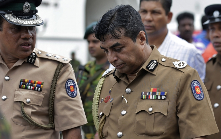 In this April 21, 2019 photo, Sri Lankan police chief Pujith Jayasundara, right, leaves after an inspection at St. Anthony's church, one of the sites of Easter Sunday explosions in Colombo, Sri Lanka. Sri Lankan police on Tuesday arrested the country's police chief, currently on compulsory leave, and its former defense secretary for alleged negligence leading to the Easter Sunday bombings that killed more than 250 people at churches and hotels. (AP Photo/Eranga Jayawardena)