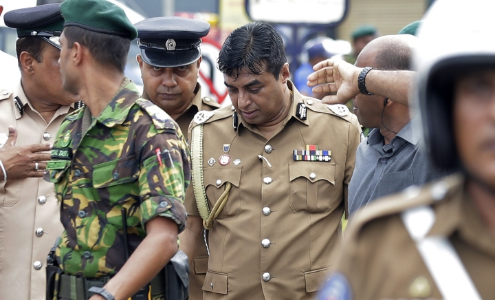 In this April 21, 2019 photo, Sri Lankan police chief Pujith Jayasundara, center, leaves after an inspection at St. Anthony's church, one of the sites of Easter Sunday explosions in Colombo, Sri Lanka. Sri Lankan police on Tuesday arrested the country's police chief, currently on compulsory leave, and its former defense secretary for alleged negligence leading to the Easter Sunday bombings that killed more than 250 people at churches and hotels. (AP Photo/Eranga Jayawardena)