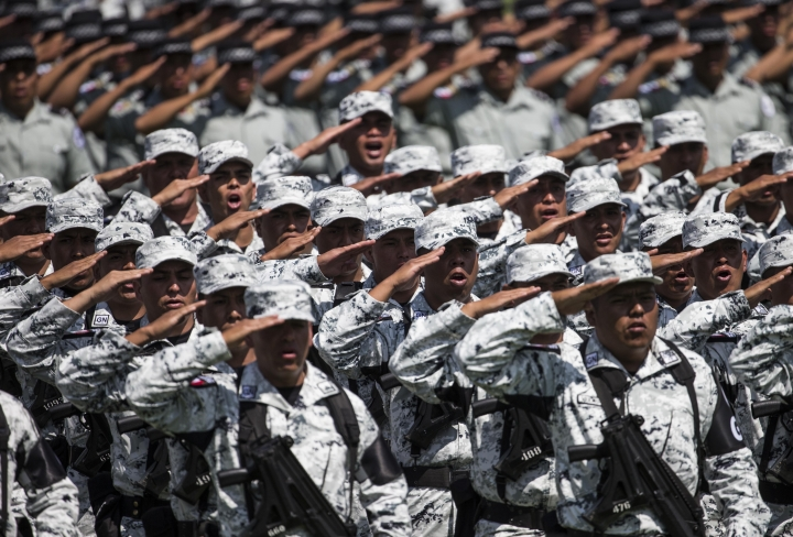 In this June 30, 2019 photo, National Guard soldiers salute as the new force is presented during a ceremony at a military field in Mexico City. Hundreds of Mexican federal police gathered at a police command center in the capital's Iztapalapa borough, Wednesday, July 2, to protest against plans to force them into the newly formed National Guard.(AP Photo/Christian Palma)