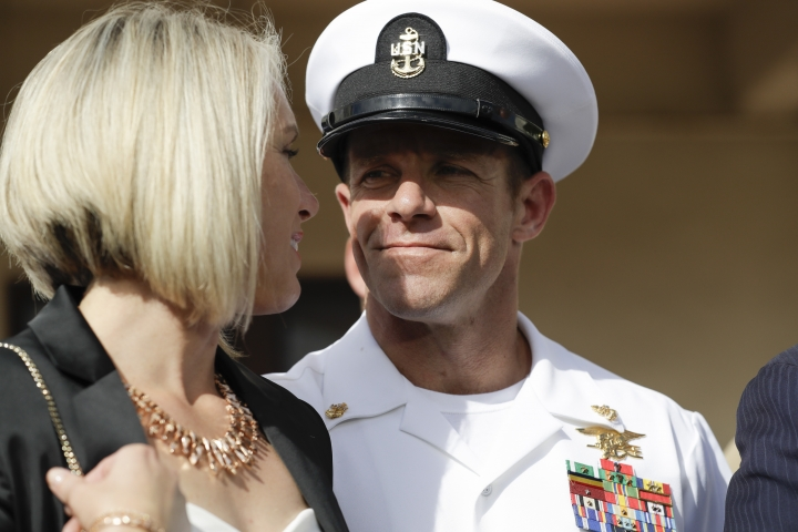 Navy Special Operations Chief Edward Gallagher, right, walks with his wife, Andrea Gallagher as they leave a military court on Naval Base San Diego, Tuesday, July 2, 2019, in San Diego. A military jury acquitted the decorated Navy SEAL Tuesday of murder in the killing of a wounded Islamic State captive under his care in Iraq in 2017. (AP Photo/Gregory Bull)