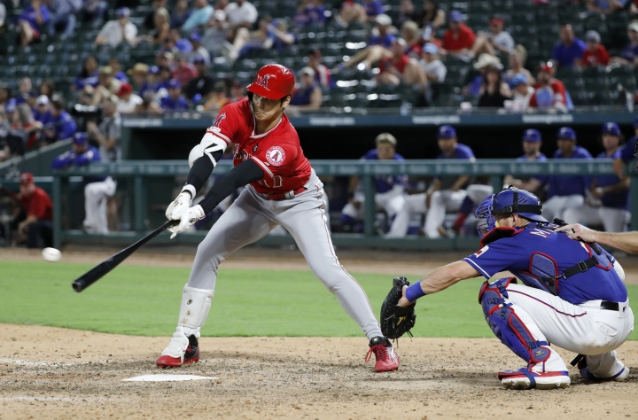 Los Angeles Angels' Shohei Ohtani connects for a single as Texas Rangers catcher Jeff Mathis watches in the eighth inning of a baseball game in Arlington, Texas, Tuesday, July 2, 2019. (AP Photo/Tony Gutierrez)