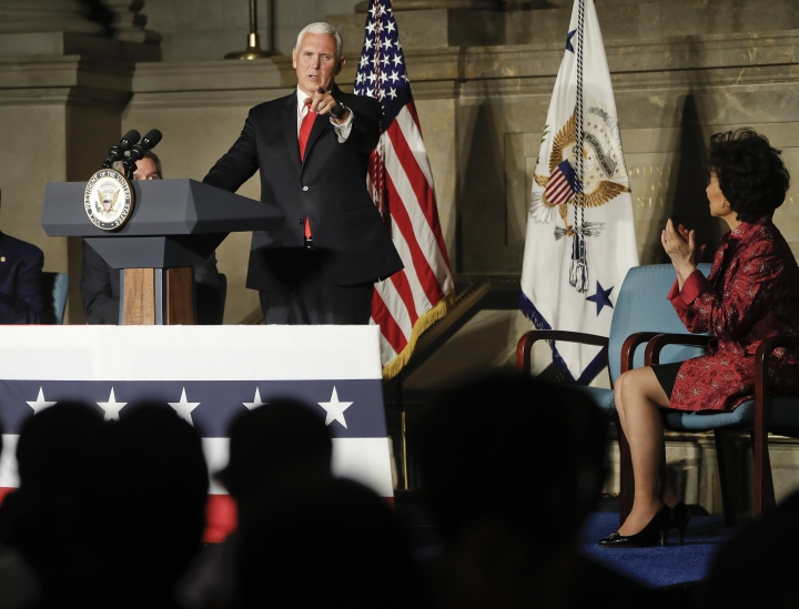 Vice President Mike Pence, points to new naturalized citizens while speaking at a naturalization ceremony in celebration of Independence Day at the National Archives in Washington, Thursday, July 4, 2019. Also on stage is Secretary of Transportation Elaine Chao, right seated. (AP Photo/Pablo Martinez Monsivais)