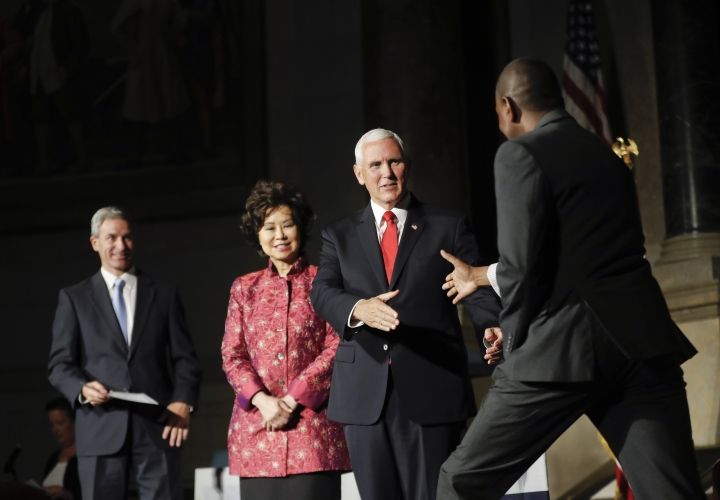 Vice President Mike Pence, center, greets a new naturalized citizen on stage at a naturalization ceremony in celebration of Independence Day at the National Archives in Washington, Thursday, July 4, 2019. Also at the event is Acting Director, US Immigration and Immigration Services, Kenneth T. Cuccinelli, left, and Secretary of Transportation Elaine Chao, second from the left. (AP Photo/Pablo Martinez Monsivais)