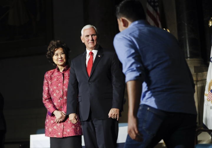Vice President Mike Pence, center, and Transportation Secretary Elaine Chao, left, greet on stage a new naturalized citizens during a naturalization ceremony in celebration of Independence Day at the National Archives in Washington, Thursday, July 4, 2019. (AP Photo/Pablo Martinez Monsivais)