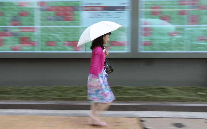 In this June 18, 2019, photo, a woman walks by an electronic stock board of a securities firm in Tokyo. Asian stocks fell Friday as investors waited for American employment data and details of U.S.-Chinese trade talks. (AP Photo/Koji Sasahara)