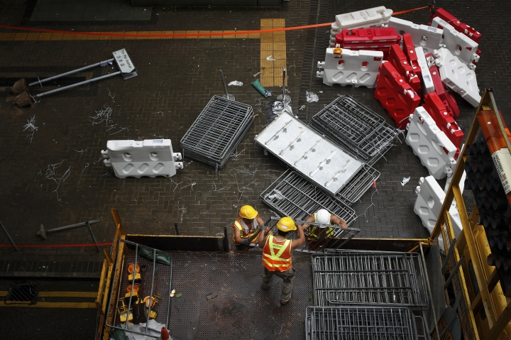 Workers load barriers used by protesters into a truck near the Legislative Council building in Hong Kong, Wednesday, July 3, 2019. A pro-democracy lawmaker who tried to stop Hong Kong protesters from breaking into the legislature this week says China will likely use the vandalizing of the building as a reason to step up pressure on the Chinese territory. (AP Photo/Andy Wong)