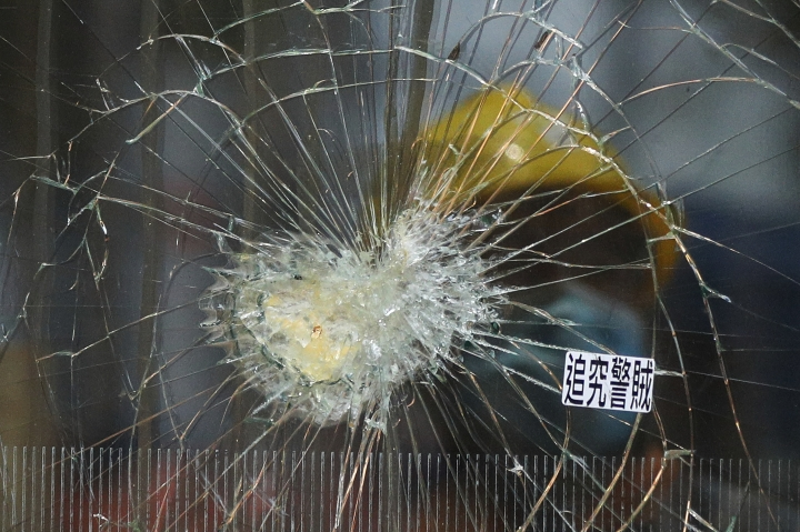 A worker is reflected on a broken glass panel damaged by protesters at the Legislative Council building in Hong Kong, Wednesday, July 3, 2019. A pro-democracy lawmaker who tried to stop Hong Kong protesters from breaking into the legislature this week says China will likely use the vandalizing of the building as a reason to step up pressure on the Chinese territory. (AP Photo/Andy Wong)