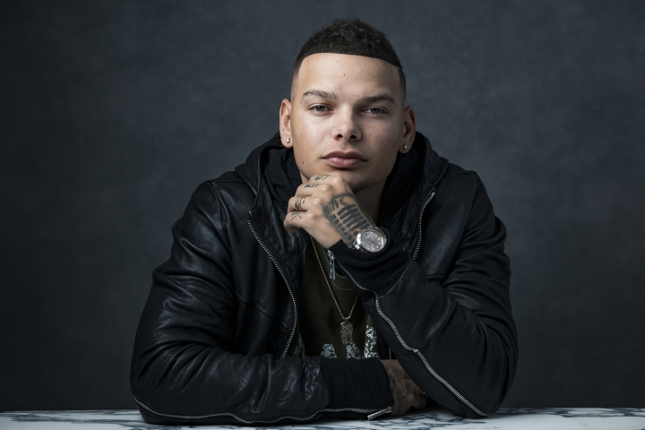 "FILE - In this Nov. 7, 2018 file photo, country singer Kane Brown poses for a portrait in New York. Brown says his new single ""Homesick"" may have been written about his own experiences of life on the road traveling and being away from his loved ones, but military families have really connected to it, too. His song is dedicated to military families and the music video features reunion videos of service members surprising their families and returning home. (Photo by Drew Gurian/Invision/AP, File)"