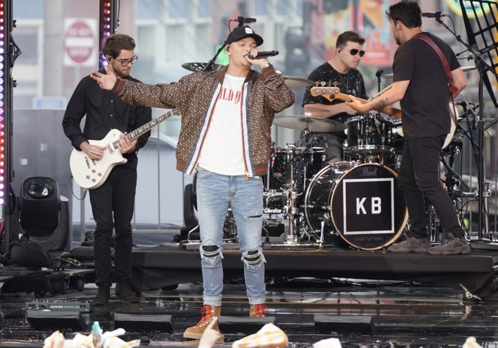 """FILE - This June 5, 2019 file photo shows Kane Brown performing """"Short Skirt Weather"""" at the CMT Music Awards in Nashville, Tenn. Brown says his new single """"Homesick"""" may have been written about his own experiences of life on the road traveling and being away from his loved ones, but military families have really connected to it, too. His song is dedicated to military families and the music video features reunion videos of service members surprising their families and returning home. (AP Photo/Sanford Myers, File)"""