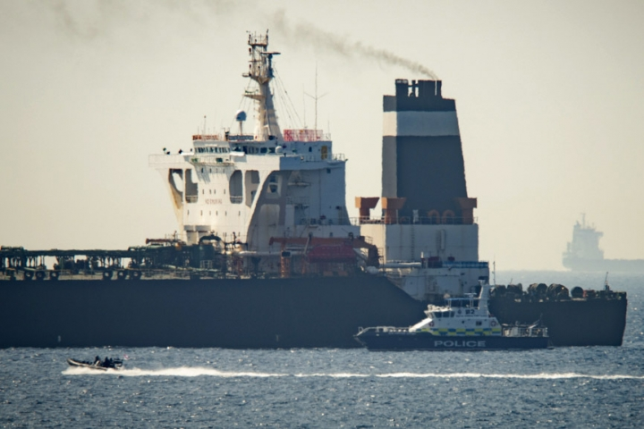 Royal Marine patrol vessel is seen beside the Grace 1 super tanker in the British territory of Gibraltar, Thursday, July 4, 2019. Authorities in Gibraltar said they intercepted Thursday an Iranian supertanker believed to be breaching European Union sanctions by carrying a shipment of Tehran's crude oil to war-ravaged Syria. (AP Photo/Marcos Moreno)
