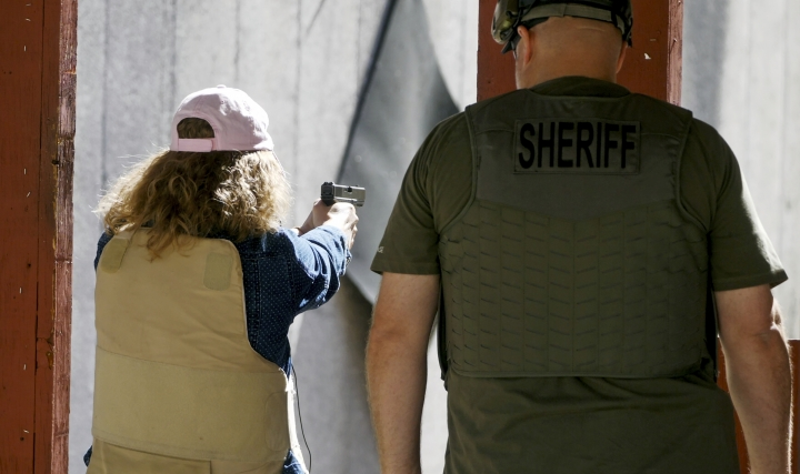 In this Saturday, June 29, 2019, photo, Cindy Bullock, Timpanogos Academy secretary, participates in shooting drills at the Utah County Sheriff's Office shooting range during the teacher's academy training, in Spanish Fork Canyon, Utah. About 30 teachers in Utah are spending their summer learning how to stuff wounds and shoot guns as part of a training held by police to prepare educators for an active shooter scenario in their schools. (AP Photo/ Rick Bowmer)