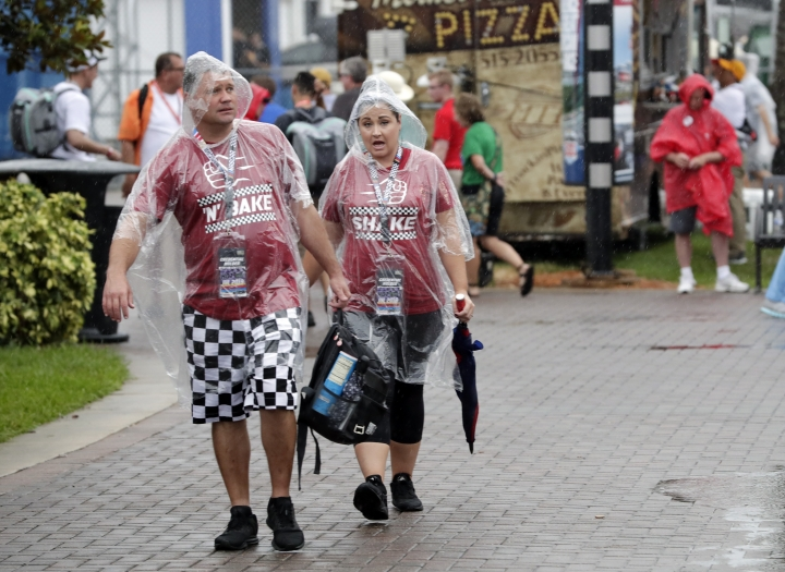 Fans walk through the Fan Zone during a weather delay of activities before the NASCAR Cup Series auto race at Daytona International Speedway, Saturday, July 6, 2019, in Daytona Beach, Fla. (AP Photo/John Raoux)