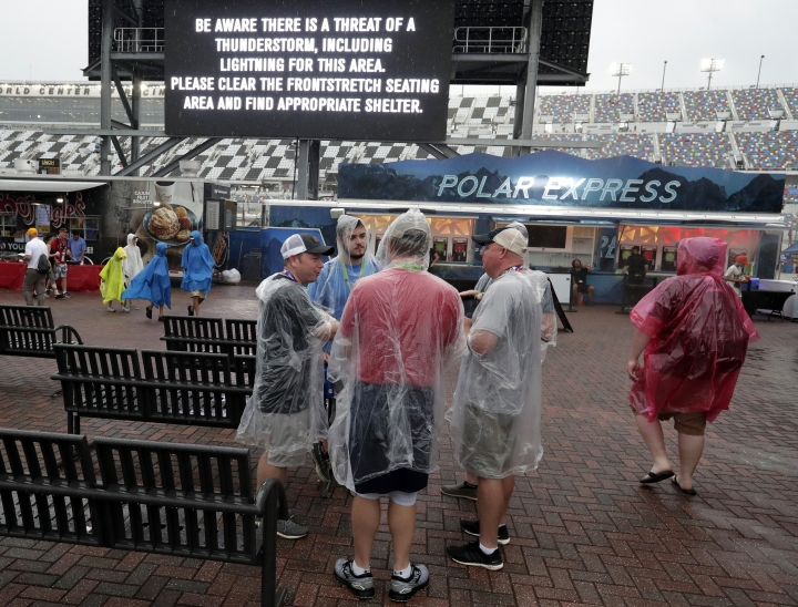 Race fans brave the weather despite warnings on a monitor during a delay before a NASCAR Cup Series auto race at Daytona International Speedway, Saturday, July 6, 2019, in Daytona Beach, Fla. (AP Photo/John Raoux)
