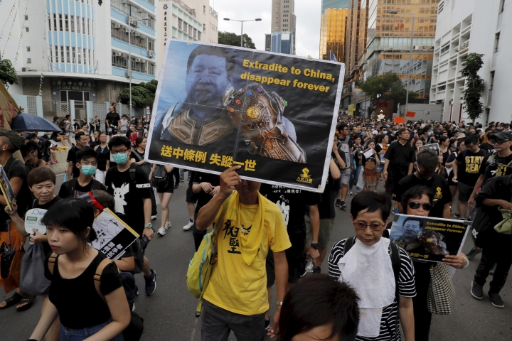 A protester holds a card depicting Chinese President Xi Jinping wielding the Thanos Infinity Gauntlet from the Avengers movie during a march in Hong Kong on Sunday, July 7, 2019. Thousands of people, many wearing black shirts and some carrying British flags, were marching in Hong Kong on Sunday, targeting a mainland Chinese audience as a month-old protest movement showed no signs of abating. (AP Photo/Kin Cheung)