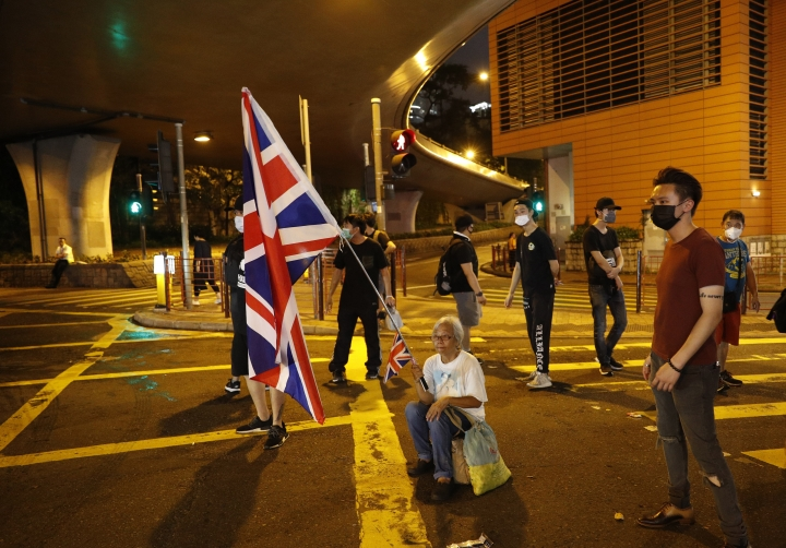Protesters block a road after a march against government's policy on the extradition bill in Hong Kong Sunday, July 7, 2019. Protesters in Hong Kong are taking their message to visitors from mainland China on Sunday in a march to a high-speed rail station that connects to Guangdong city and other mainland destinations. (AP Photo/Vincent Yu)