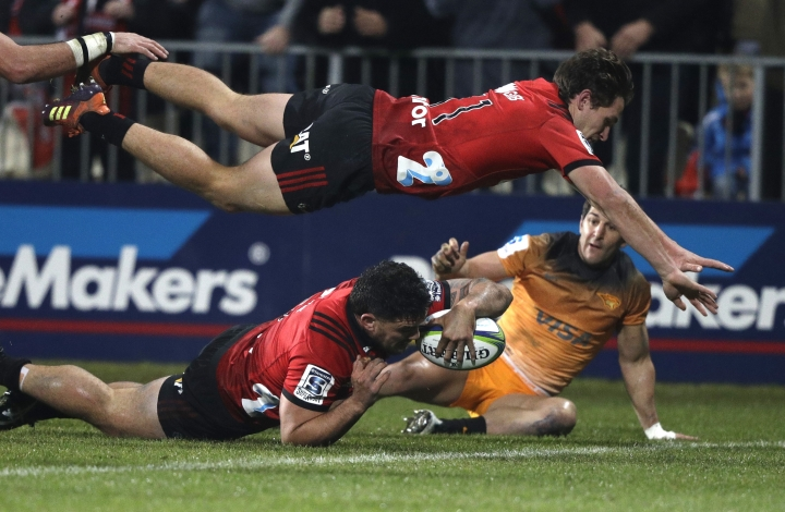 Crusaders Codie Taylor dives across the line to score a try as teammate George Bridge is airborne above him during the Super Rugby final between the Crusaders and the Jaguares in Christchurch, New Zealand, Saturday, July 6, 2019. (AP Photo/Mark Baker)
