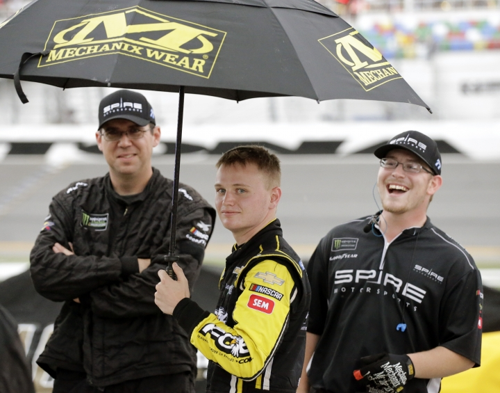 Justin Haley, center, waits on pit road in the rain with crew members after the NASCAR Cup Series auto race was stopped because of weather at Daytona International Speedway, Sunday, July 7, 2019, in Daytona Beach, Fla. Haley was declared the winner a short time later. (AP Photo/Terry Renna)