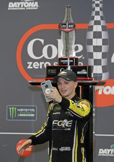 Justin Haley takes a photo in front of his trophy after winning a NASCAR Cup Series auto race at Daytona International Speedway, Sunday, July 7, 2019, in Daytona Beach, Fla. (AP Photo/Terry Renna)