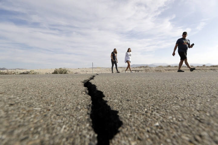 Visitors cross highway 178 next to a crack left on the road by an earthquake Sunday, July 7, 2019, near Ridgecrest, Calif. (AP Photo/Marcio Jose Sanchez)