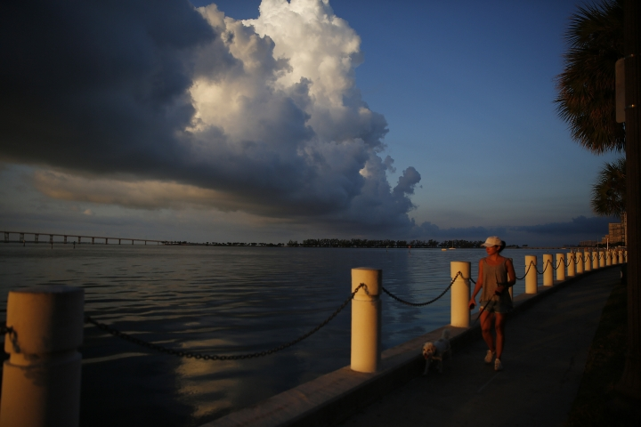 In this June 4, 2019, photo a woman walks her dog along the water near downtown Miami. According to a survey by The Associated Press-NORC Center for Public Affairs Research, Americans are generally satisfied with their personal finances, but many lack confidence in their ability to afford retirement, an emergency expense or even their daily living costs. (AP Photo/Brynn Anderson)