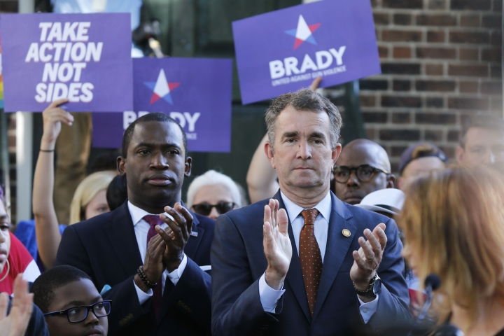 Virginia Gov. Ralph Northam, right, applauds speakers along with Richmond Mayor Levar Stoney, left, during a rally at the State Capitol in Richmond, Va., Tuesday, July 9, 2019. Governor Northam called a special session of the General Assembly to consider gun legislation in light of the Virginia Beach Shootings. (AP Photo/Steve Helber)