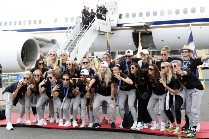 Members of the United States women's soccer team, winners of a fourth Women's World Cup, celebrate and pose with the trophy by their plane after arriving at Newark Liberty International Airport, Monday, July 8, 2019, in Newark, N.J. Julie Ertz holds the trophy, Megan Rapinoe, front right, gestures, and Alex Morgan, back left, also gestures. (AP Photo/Kathy Willens)