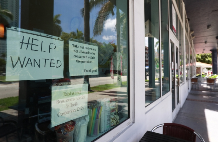 In this Monday, July 1, 2019 photo, a help wanted sign appears in the window of a restaurant in Miami. On Tuesday, July 9, the Labor Department reports on job openings and labor turnover for April. (AP Photo/Wilfredo Lee)