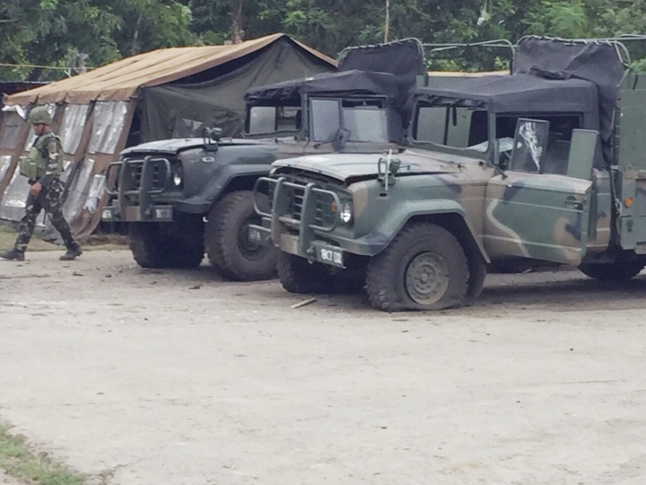 In this Friday, June 28, 2019, photo, a soldier walks past damaged military vehicles from suicide attack carried out by militants at a military camp in Indanan township, on the island of Jolo in Sulu province that killed five people and the bombers in the southern Philippines. Maj. Gen. Cirilito Sobejana told The Associated Press Tuesday, July 2, 2019, that the family of the 23-year-old militant, Norman Lasuca, has identified him as one of the bombers who detonated a bomb on Friday at the gate of an army encampment in Sulu province's Indanan town. Lasuca is the first known Filipino militant to have agreed to carry out a suicide bombing, a development that has concerned Philippine security officials. (AP Photo)