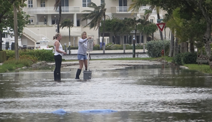 "FILE - In this Oct. 5, 2017, file photo, residents move a ""no wake,"" sign through flood waters caused by king tides in Fort Lauderdale, Fla. Federal scientists, according to a report released Wednesday, July 10, 2019, predict 40 places in the U.S. will experience higher than normal rates of so-called sunny day flooding this year due to rising sea levels and an abnormal El Nino weather system. (Joe Cavaretta/South Florida Sun-Sentinel via AP)"