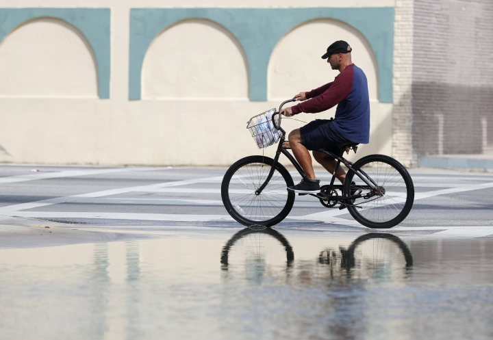 FILE - In this Oct. 9, 2018, file photo, a cyclist rides past an area flooded during a King Tide, an especially high tide, in Miami. Federal scientists, according to a report released Wednesday, July 10, 2019, predict 40 places in the U.S. will experience higher than normal rates of so-called sunny day flooding this year due to rising sea levels and an abnormal El Nino weather system. (AP Photo/Wilfredo Lee, FIle)