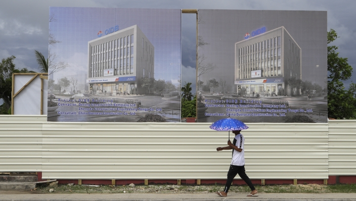 In this Wednesday, April 10, 2019, photo, a man walks past a development site for a Chinese Investment bank in Nuku'alofa, Tonga. China is pouring billions of dollars in aid and low-interest loans into the South Pacific, and even in the far-flung kingdom of Tonga there are signs that a battle for power and influence among much larger nations is heating up and could exact a toll. (AP Photo/Mark Baker)