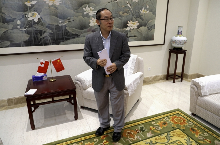 In this April 9, 2019, photo, China's ambassador to Tonga, Wang Baodong, waits to speak to The Associated Press at the embassy in Nuku'alofa, Tonga. China is pouring billions of dollars in aid and low-interest loans into the South Pacific, and even in the far-flung kingdom of Tonga there are signs that a battle for power and influence among much larger nations is heating up and could exact a toll. (AP Photo/Mark Baker)