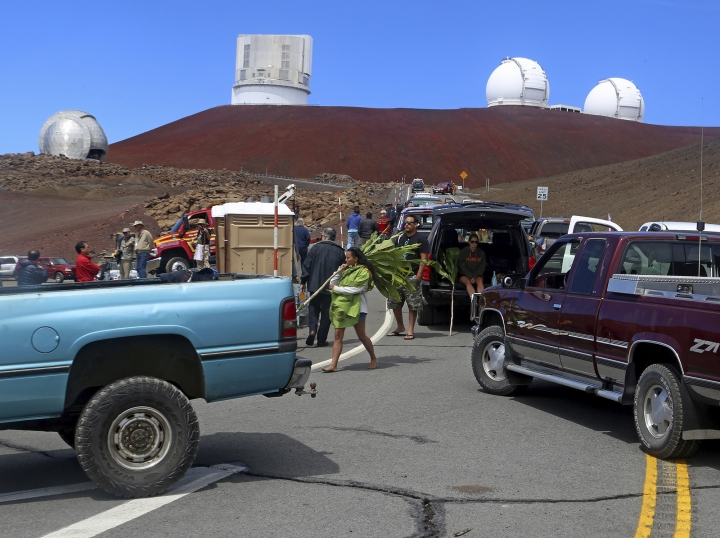 FILE - In this Oct. 7, 2014, file photo, protesters block vehicles from getting to the Thirty Meter Telescope groundbreaking ceremony site at Mauna Kea, Hawaii. Construction on the giant telescope will start again next week after lengthy court battles and passionate protests from those who say building it on Hawaii's tallest mountain will desecrate land sacred to some Native Hawaiians. State officials announced Wednesday, July 10, 2019, that the road to the top of Mauna Kea mountain on the Big Island will be closed Monday as equipment is delivered to the construction site. (Hollyn Johnson/Hawaii Tribune-Herald via AP, File)