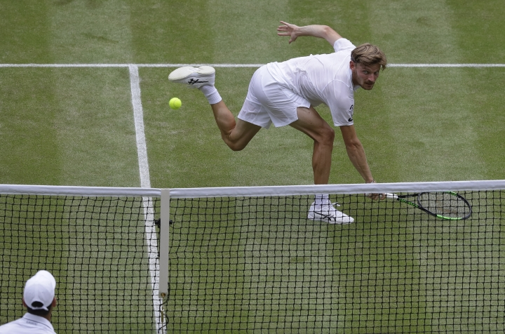 Belgium's David Goffin returns the ball to Serbia's Novak Djokovic, bottom, during a men's quarterfinal match on day nine of the Wimbledon Tennis Championships in London, Wednesday, July 10, 2019. (AP Photo/Kirsty Wigglesworth)