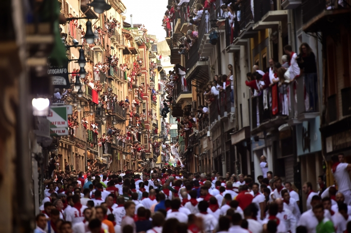 Revellers stand at the street ahead of the running of the bulls during the San Fermin Festival, in Pamplona, northern Spain, Thursday, July, 11, 2019. Revellers from around the world flock to Pamplona every year to take part in the eight days of the running of the bulls. (AP Photo/Alvaro Barrientos)