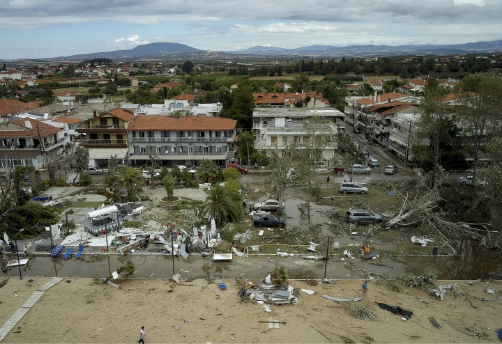 People search and clean a damaged square after a storm at Sozopoli village in Halkidiki region, northern Greece, Thursday, July 11, 2019. A search and rescue operation is underway in northern Greece for a fisherman missing after a powerful storm left six people dead, including two children, and injured more than 100. (Vassilis Konstantopoulos/InTime News via AP)