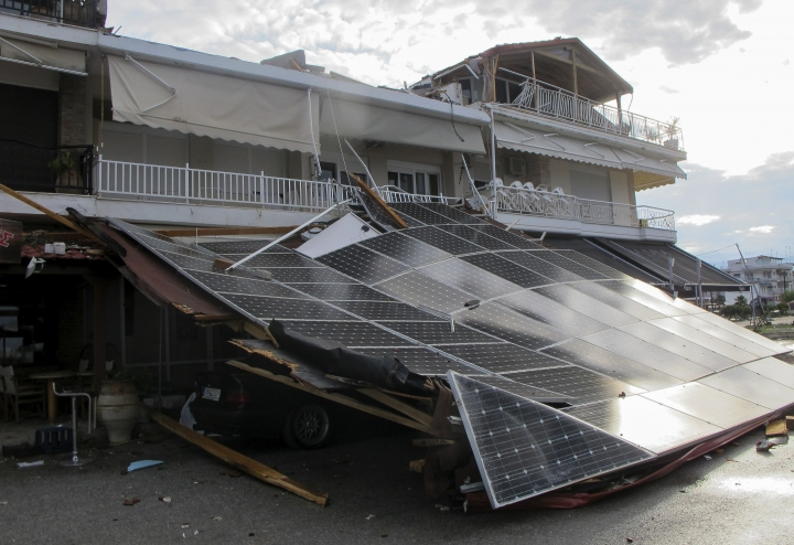 A car is seen under an outdoor shop's lean-to roof after a storm at Nea Plagia village in Halkidiki region, northern Greece on Thursday, July 11, 2019. A powerful storm hit the northern Halkidiki region late Wednesday. (Giannis Moisiadis/InTime News via AP)