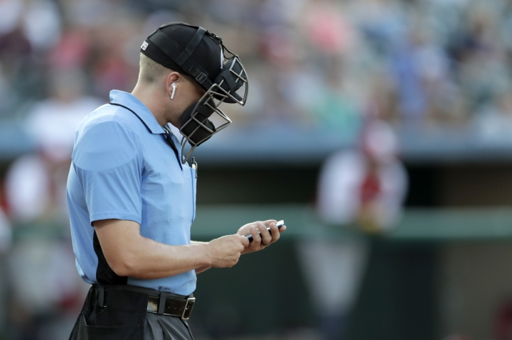 Home plate umpire Brian deBrauwere checks an iPhone while wearing an earpiece prior to the start of the Atlantic League All-Star minor league baseball game, Wednesday, July 10, 2019, in York, Pa. The umpire received information about balls and strikes with the device connected to a TrackMan computer system that uses Doppler radar. The independent Atlantic League became the first American professional baseball league to let the computer call balls and strikes during the all star game. (AP Photo/Julio Cortez)