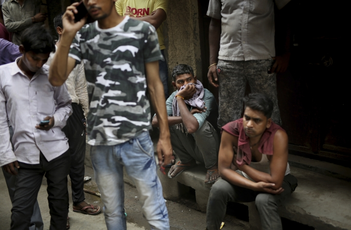 Indians gather near the site of a fire at a rubber factory in an industrial area in New Delhi, India, Saturday, July 13, 2019. Dev Dutt from the New Delhi fire office said 34 fire engines battled the fire for four hours in the city's Jhilmil industrial area. (AP Photo/Altaf Qadri)