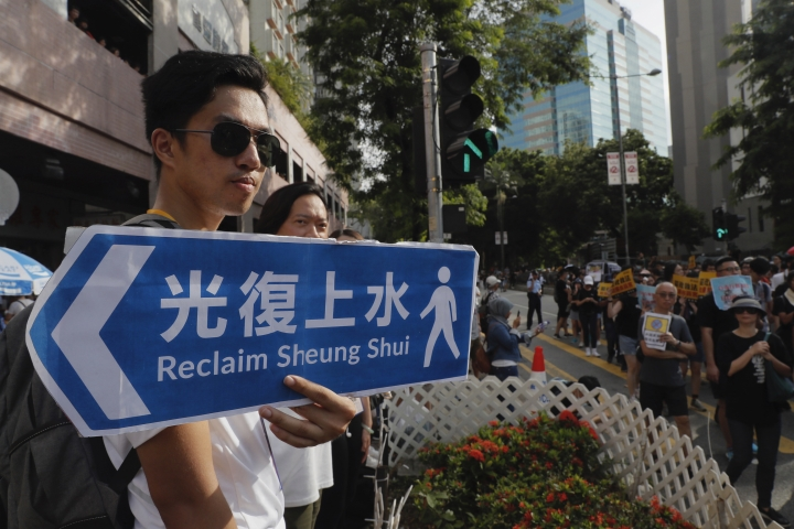 A protester holds up a protest banner in the shape of a street sign in Hong Kong Saturday, July 13, 2019. Several thousand people marched in Hong Kong on Saturday against traders from mainland China in what is fast becoming a summer of unrest in the semi-autonomous Chinese territory. (AP Photo/Kin Cheung)