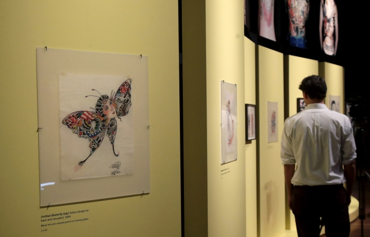 "In this Wednesday, July 10, 2019 photo, a man walks near artwork created by Ed Hardy during a media preview of ""Ed Hardy: Deeper than Skin"" at the de Young Museum in San Francisco. The exhibition opening Friday, July 12 sheds light on Hardy as a prolific artist and tattoo pioneer. (AP Photo/Jeff Chiu)"