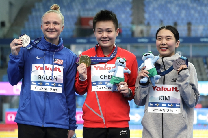 From left, Sarah Bacon of the United States, Chen Yiwen of China, and Suji Kim of South Korea hold their medals after competing in the women's 1 meter springboard diving final competition at the World Swimming Championships in Gwangju, South Korea, Saturday, July 13, 2019. (AP Photo/Mark Schiefelbein)