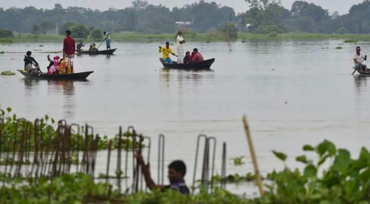 In this Friday, July 12, 2019 photo, Indian villagers cross floodwaters on country boats in Ashighar village, Morigaon district, in the northeastern Indian state of Assam. Rain-triggered floods and mudslides have left a trail of destruction across northeastern India, killing at least a dozen people and affecting over a million, officials said Saturday. (AP Photo)