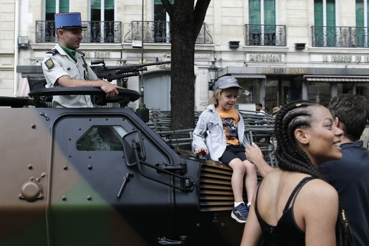 A child sits on a tank before Bastille Day parade Sunday, July 14, 2019 near the Champs Elysees avenue in Paris. (AP Photo/Rafael Yaghobzadeh)