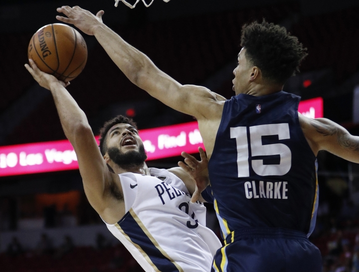 New Orleans Pelicans' Kenrich Williams, left, shoots around Memphis Grizzlies' Brandon Clarke, right, during the first half of an NBA summer league basketball game Sunday, July 14, 2019, in Las Vegas. (AP Photo/John Locher)