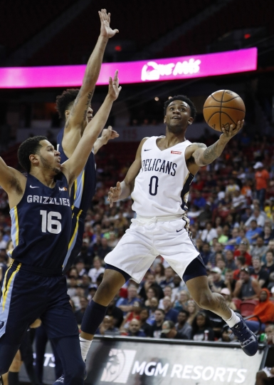 New Orleans Pelicans' Nickeil Alexander-Walker shoots around Memphis Grizzlies' Tyler Harvey during the first half of an NBA summer league basketball game Sunday, July 14, 2019, in Las Vegas. (AP Photo/John Locher)
