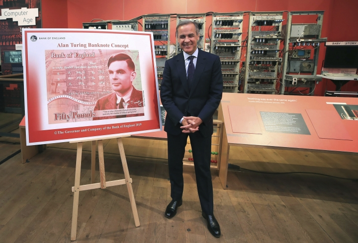 "Governor of the Bank of England, Mark Carney poses for a photo with the artwork for the concept of the new 50 pound notes, after announcing that Second World War code-breaker Alan Turing has been selected to feature on the new notes, at the Science and Industry Museum, in Manchester, England, Monday July 15, 2019. The Bank of England has chosen codebreaker and computing pioneer Alan Turing as the face of the country's new 50 pound note. Governor Mark Carney said Monday that Turing was ""a giant on whose shoulders so many now stand."" Turing's work cracking Nazi Germany's secret communications helped win World War II, but after the war he was prosecuted for homosexuality, and died in 1954 after eating an apple laced with cyanide. (Peter Byrne/PA via AP)"