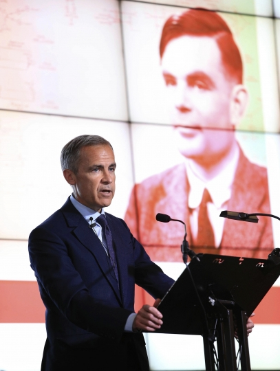 "Governor of the Bank of England, Mark Carney speaks, during the announcement that Second World War code-breaker Alan Turing has been selected to feature on the new 50 pound notes, at the Science and Industry Museum, in Manchester, England, Monday July 15, 2019. The Bank of England has chosen codebreaker and computing pioneer Alan Turing as the face of the country's new 50 pound note. Governor Mark Carney said Monday that Turing was ""a giant on whose shoulders so many now stand."" Turing's work cracking Nazi Germany's secret communications helped win World War II, but after the war he was prosecuted for homosexuality, and died in 1954 after eating an apple laced with cyanide. (Peter Byrne/PA via AP)"